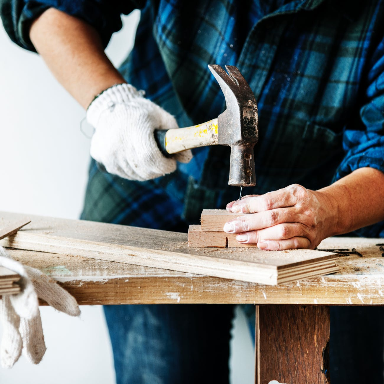 Image contains a man hammering a nail in wood.