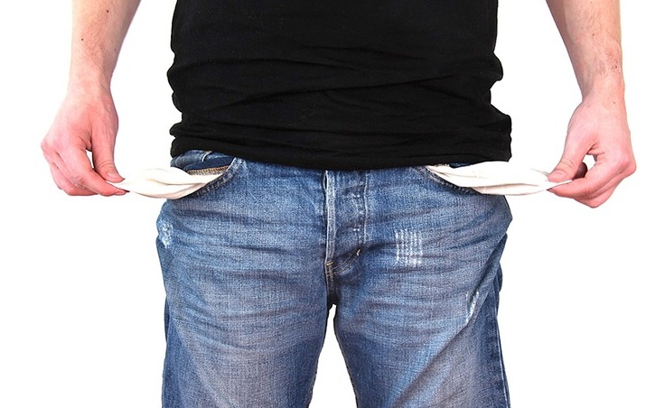 Image contains a man holding the inside of his pockets out.